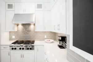 White inset kitchen cabinets with stainless steel stove and hood