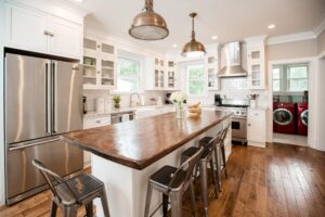Natural wood tone countertop on island with 4 stools