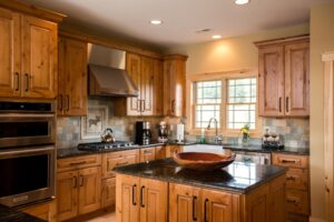 Natural wood tone kitchen cabinets with center island and double oven