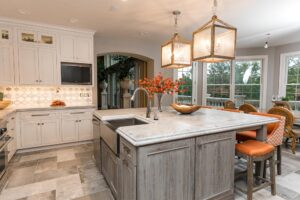 Grey washed wood tone island paired with white inset cabinets