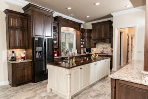 Two tone kitchen with dark wood tone cabinets and white island