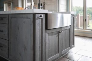 Stainless steel farmhouse sink in gray cabinet island