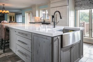 Gray washed island cabinets with farmhouse sink in island