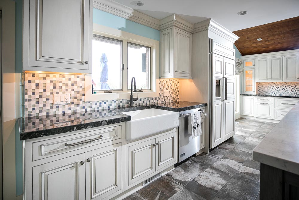 White cabinets with white farmhouse sink and gray countertop