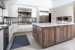 White kitchen cabinets with wood tone island