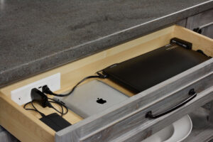 Charging station for electronics within cabinet drawer